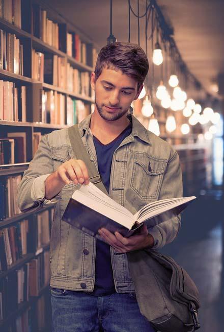 maturant studuje knihu v knižnici na maturitu